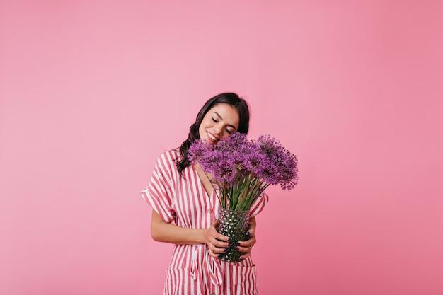 아주 어린 소녀는 꽃의 향기를 즐깁니다. 트렌디 한 핑크 탑의 곱슬 모델의 스냅 샷.