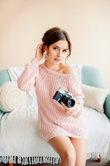 A pretty young girl of european appearance holds in her hand a vintage camera in a cozy house