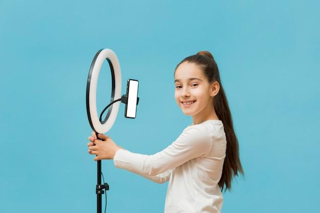 Хорошенькая молодая девушка готовится к записи видео