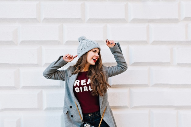 Pretty young girl in grey coat on grey wall . she wears knitted hat, keeps hands overhead, looks happy.