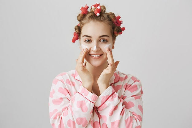 Pretty young girl in hair curlers and pajama apply facial cream