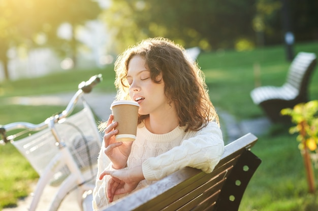 Pretty young girl having coffee in the park in the morning