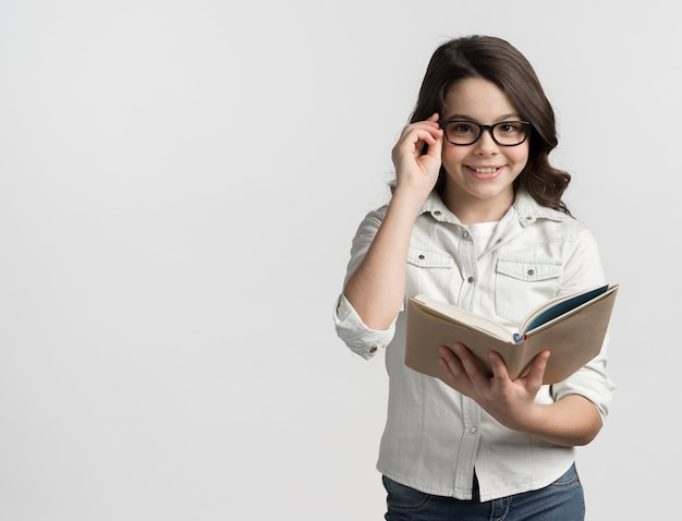 Хорошенькая молодая девушка держит книгу с копией пространства