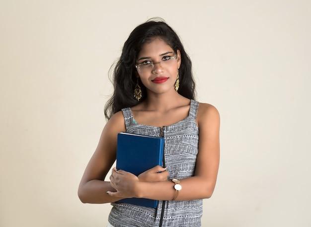 Довольно молодая девушка держит и позирует с книгой