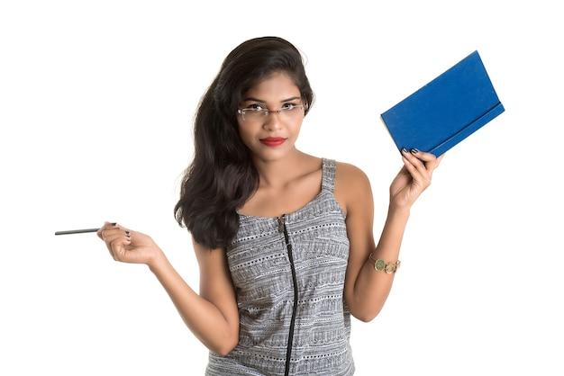 Довольно молодая девушка держит книгу и позирует на белой стене