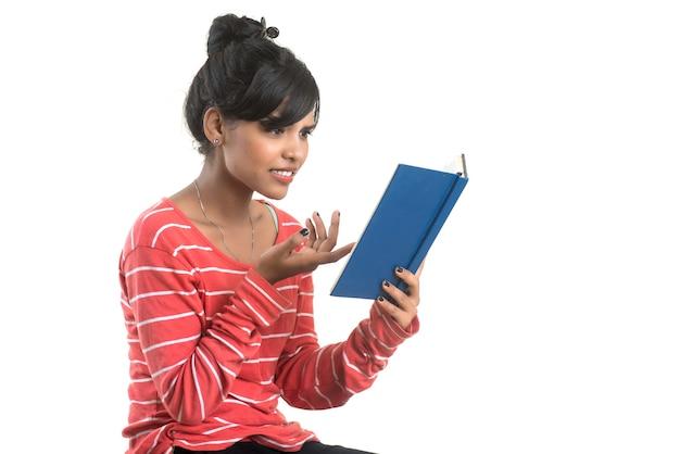 Довольно молодая девушка держит книгу и позирует