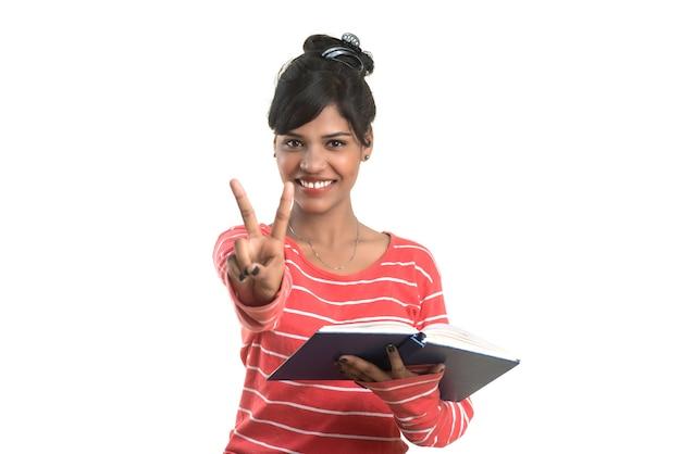 Довольно молодая девушка держит книгу и показывает знак победы