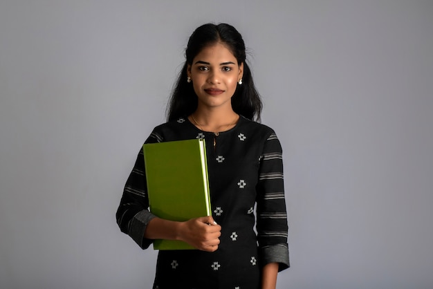 Pretty young girl holding book and posing on grey background