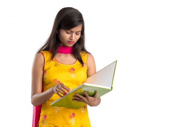 Pretty young girl holding book and posing on white surface