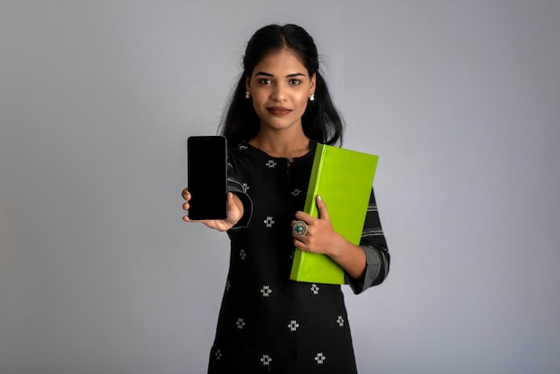 Pretty young girl holding book and using mobile on grey background