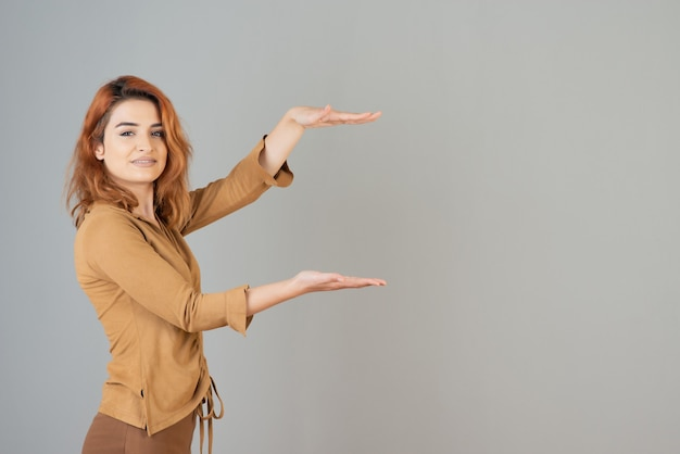Pretty young girl holding her hands gesturing measurement