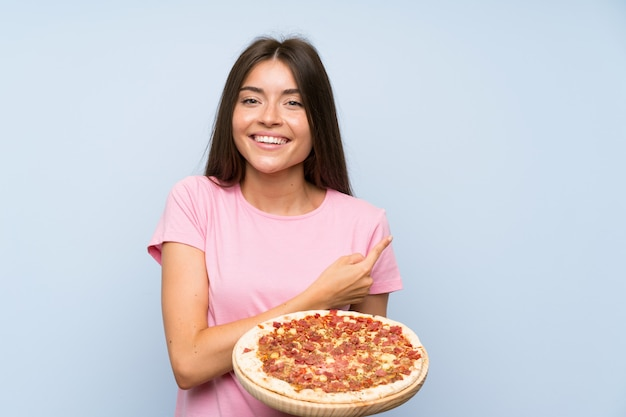 Pretty young girl holding a pizza over isolated blue wall pointing to the side to present a product