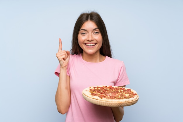 Pretty young girl holding a pizza over isolated blue wall pointing up a great idea