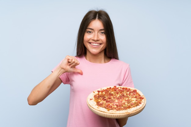 Pretty young girl holding a pizza over isolated blue wall proud and self satisfied
