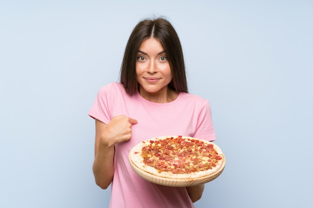 Pretty young girl holding a pizza over isolated blue wall with surprise facial expression