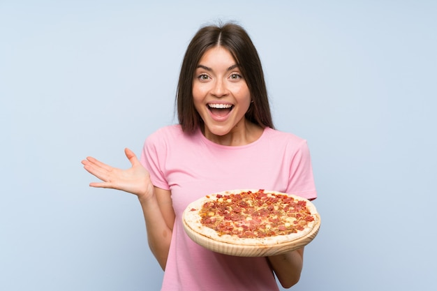 Pretty young girl holding a pizza with shocked facial expression