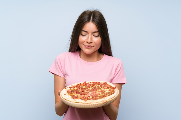 Pretty young girl holding a pizza