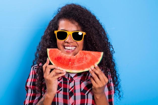 그녀의 얼굴 앞에서 수 박 조각을 들고 아주 어린 소녀. 고립 된 웃는 아프리카 계 미국인 여자의 초상화 건강 & 행복