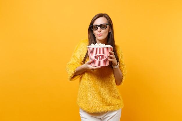 3d 아이맥스 안경을 쓴 예쁜 소녀가 영화 영화를 보고, 양동이를 들고, 밝은 노란색 배경에 격리된 팝콘을 킁킁거리고 있습니다. 영화, 라이프 스타일 개념에서 사람들은 진실한 감정. 광고 영역입니다.