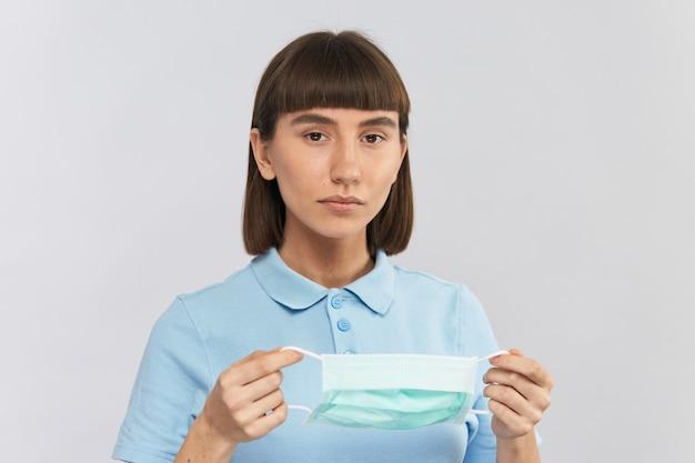 Симпатичная молодая девушка в синей рубашке держит стерильную одноразовую маску, женщина с защитной маской от коронавируса или covid-19