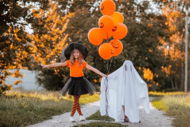 Симпатичная молодая девушка в костюме ведьмы позирует с маленьким ребенком в костюме забавного привидения на улице с оранжевыми воздушными шарами. концепция партии.