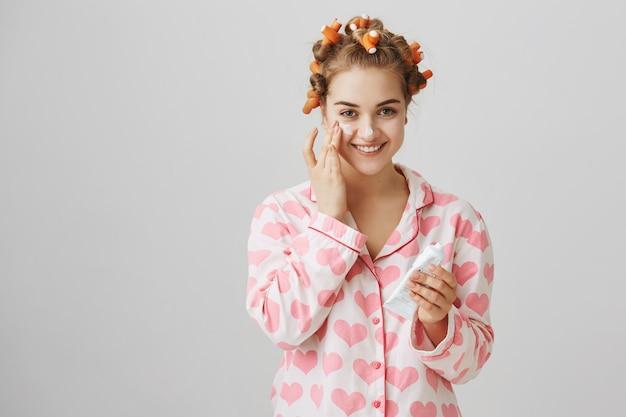 ヘアカーラーとパジャマのかなり若い女の子が顔のクリームを塗る