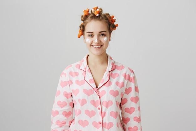 머리카락 curlers 및 파자마에 아주 어린 소녀는 얼굴 크림을 적용