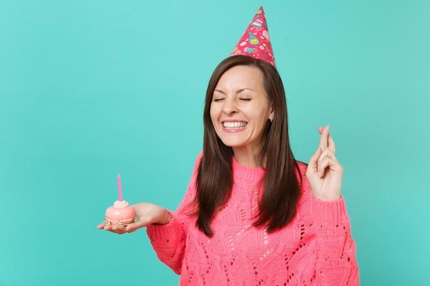 분홍색 스웨터 생일 모자를 쓴 예쁜 소녀가 파란 벽 배경에 촛불을 들고 손으로 케이크를 들고 손가락을 꼬고 눈을 감고 있습니다. 사람들이 라이프 스타일 개념입니다. 복사 공간을 비웃습니다.