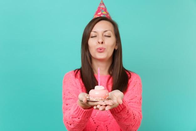 파란색 배경 스튜디오 초상화에 격리된 손에 케이크에 촛불을 불고 눈을 감고 니트 핑크 스웨터 생일 모자에 예쁜 어린 소녀. 사람들이 라이프 스타일 개념입니다. 복사 공간을 비웃습니다.