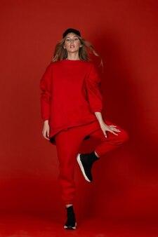 赤いスタジオの背景にポーズをとって赤いスポーツスーツのかわいい若い女の子