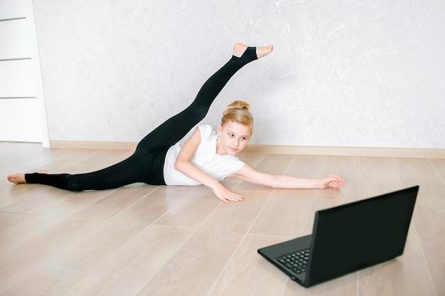 ノートパソコンでオンラインビデオを見て、自宅でフィットネス演習を行うスポーツウェアのかなり若い女の子。パーソナルトレーナー、社会的距離または自己分離、オンライン教育の概念との遠隔トレーニング