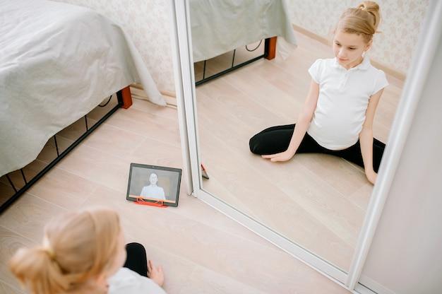 Довольно молодая девушка в спортивной одежде смотрит онлайн-видео на ноутбуке и делает фитнес-упражнения дома.