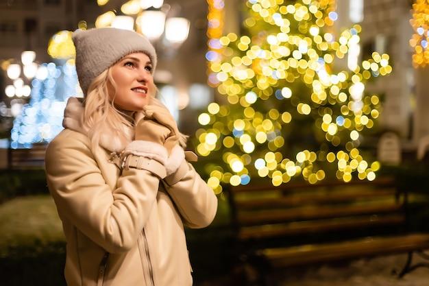 크리스마스 조명에기도하는 겨울 옷에 예쁜 어린 소녀