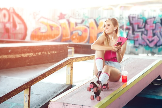 Pretty young girl is looking to the left and smiling. she is holding phone in hands and listening to music. also there is a cup of drink besides her.