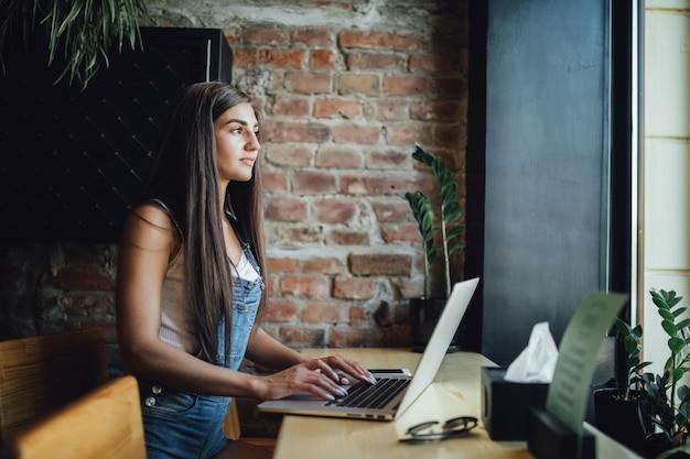 La ragazza graziosa è seduta nel caffè davanti alla finestra, lavora sul suo laptop e beve una bevanda fresca