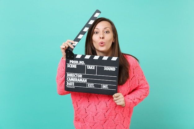 Pretty young girl in knitted pink sweater blowing sending air kisses hold in hand classic black film making clapperboard isolated on blue wall background. people lifestyle concept. mock up copy space.