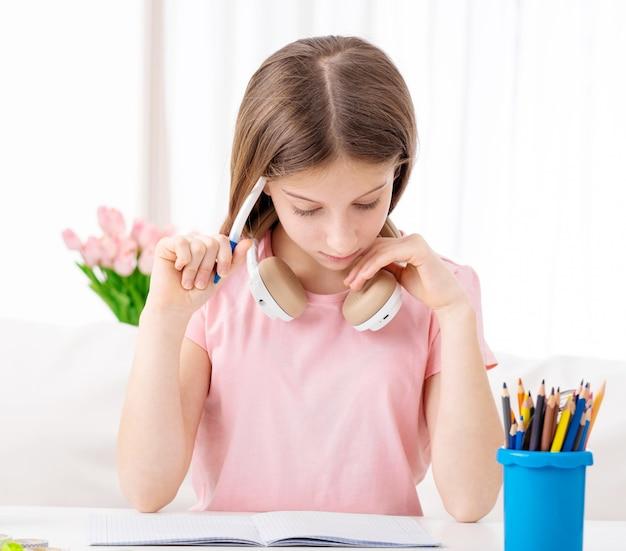 Хорошенькая молодая девушка учится в наушниках