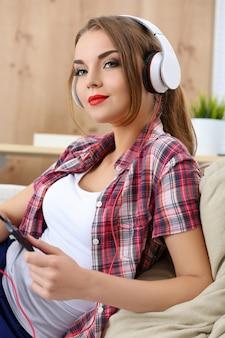 かなり若い女の子が彼女の電話で音楽を聴く