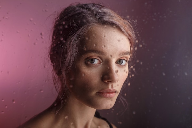 Pretty young girl looks into camera on purple background. blurry drops of water run down the glass in front of her face