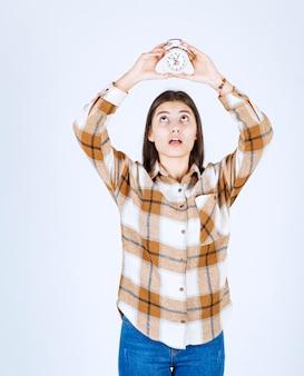 頭上に目覚まし時計を保持しているかなり若い女の子モデル。