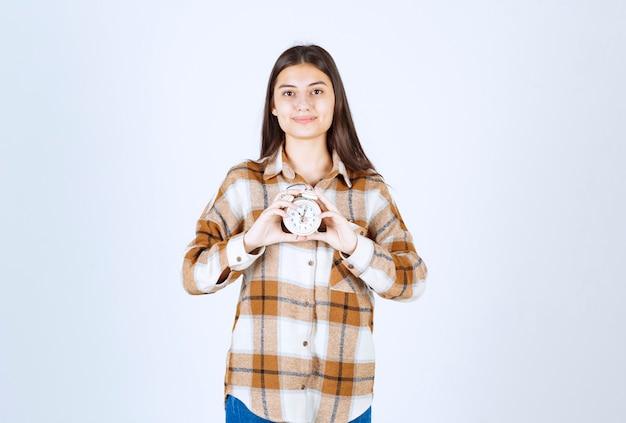 目覚まし時計を保持しているかなり若い女の子モデル。