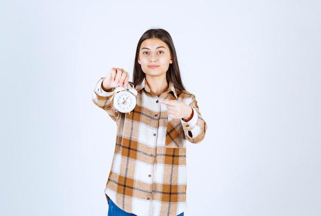 目覚まし時計を指しているかなり若い女の子モデル。