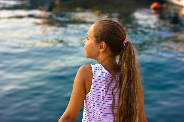 Pretty young girl near the mediterranean sea looking forward . a