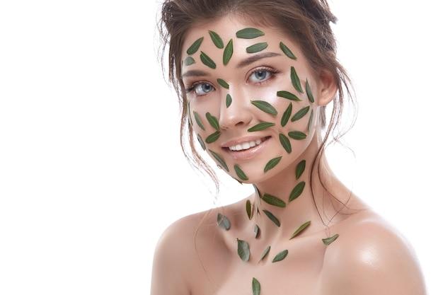 그녀의 얼굴에 잎과 흰색 바탕에 아주 어린 소녀