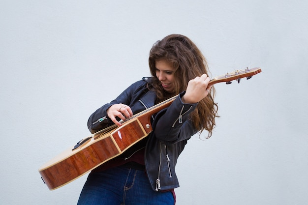 Pretty young girl playing guitar emotionally