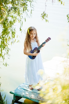 Pretty young girl playing ukulele in the park