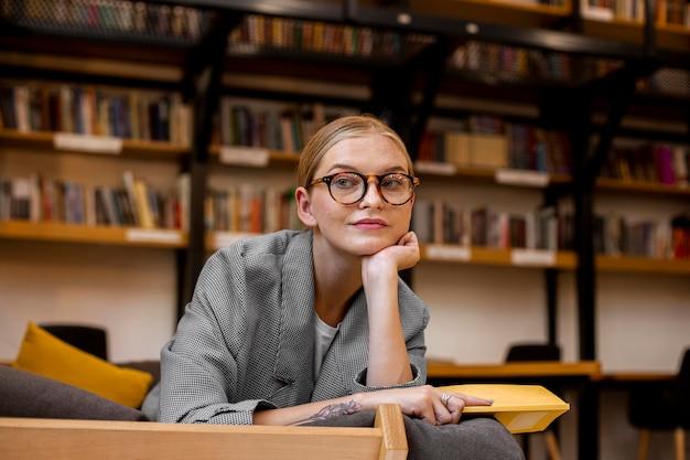Довольно молодая девушка позирует в библиотеке