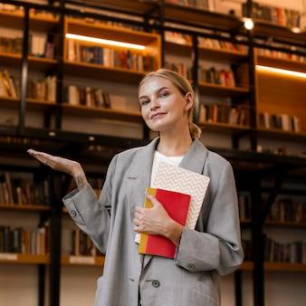 Ragazza graziosa che propone alla biblioteca