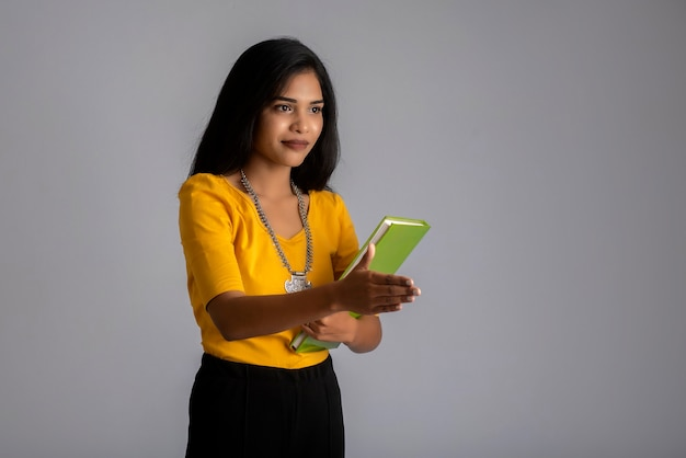 Pretty young girl posing with the book on grey wall