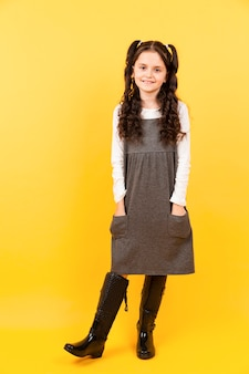 Pretty young girl posing with yellow background